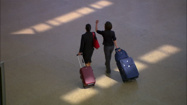 high angle wide shot two businesswomen walking through airport with luggage/ seattle - meno di 10 secondi video stock e b–roll
