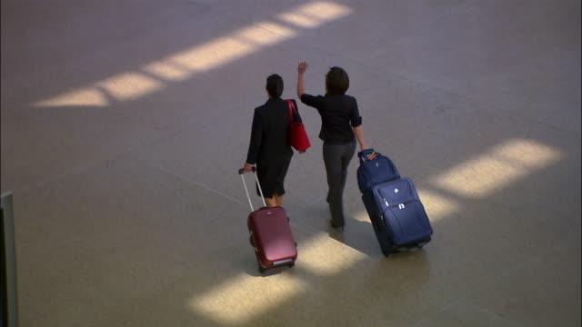 vídeos de stock, filmes e b-roll de high angle wide shot two businesswomen walking through airport with luggage/ seattle - menos de 10 segundos