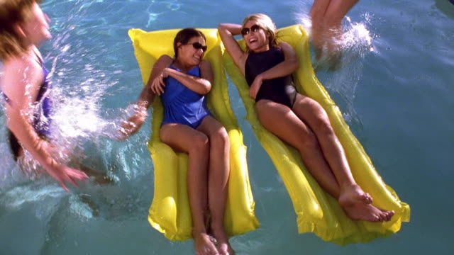 high angle wide shot two teen girls on rafts in pool with two other girls jumping in and splashing them / tucson, arizona - swimwear stock videos & royalty-free footage