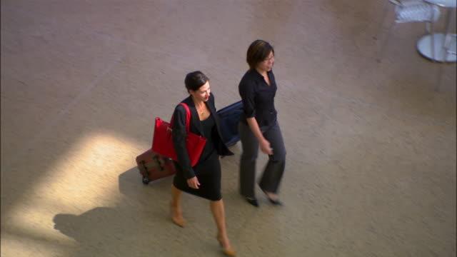 high angle wide shot two women walking through airport pulling luggage/ seattle - 引く点の映像素材/bロール