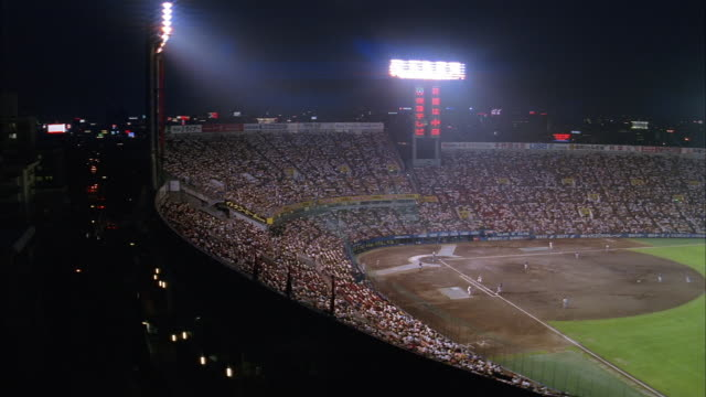 high angle wide shot view of infield during night game in baseball stadium / japan - baseball sport stock videos & royalty-free footage
