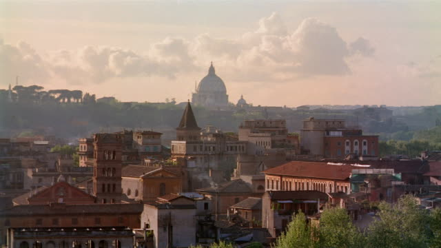 vidéos et rushes de high angle wide shot view of roofops of buildings with silhouette of dome of st. peter's in background / rome, italy - 1980 1989