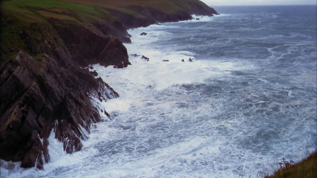 high angle wide shot waves crashing by cliffs on coast / croagh patrick, ireland - 2002 stock videos & royalty-free footage