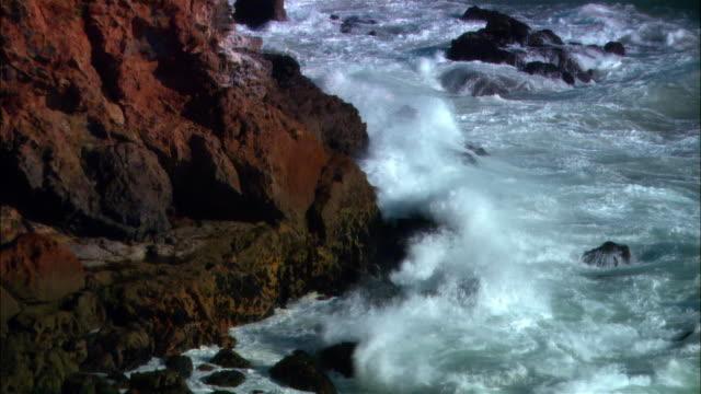 vídeos de stock e filmes b-roll de high angle wide shot waves crashing on rocky coast/ malibu, california - pacífico norte