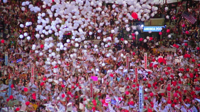 high angle wide shot white balloons + confetti falling on delegates at Democratic National Convention / Los Angeles