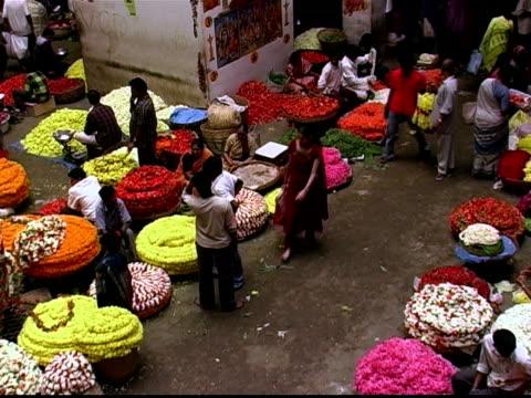 High angle wide shot woman walking through flower market / looking at garland