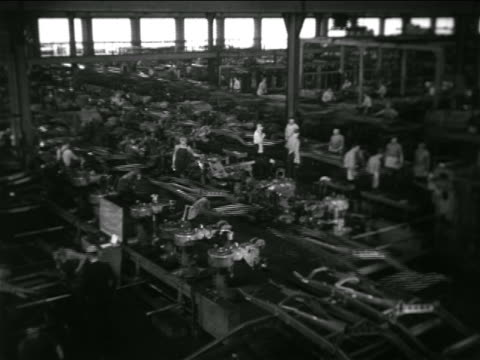 b/w 1936 high angle wide shot workers + machinery in large room in chevrolet car factory - production line stock videos & royalty-free footage