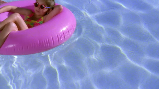 high angle wide shot young girl floating on pink inner tube in pool with drink in hand / tucson, arizona - inner tube stock videos and b-roll footage