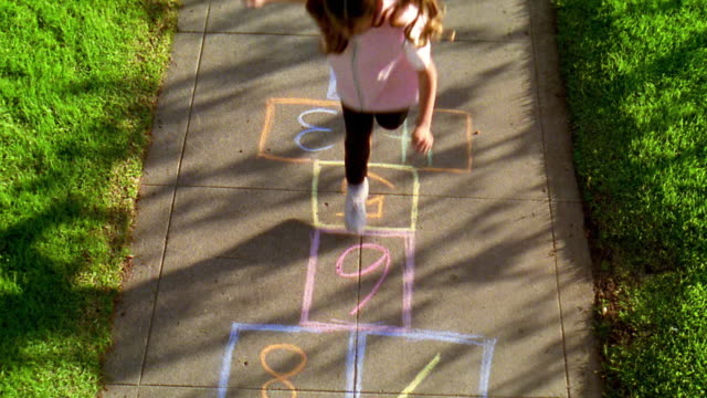 high angle wide shot young girl with pigtails playing hopscotch on sidewalk - leisure games stock videos & royalty-free footage