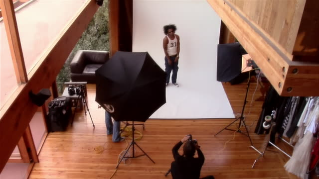 high angle wide shot young man posing for photographer and dancing in studio - 2000s style点の映像素材/bロール