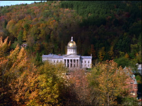 high angle wide shot zoom in gold domed capitol building surrounded by autumn trees / Montpelier, Vermont