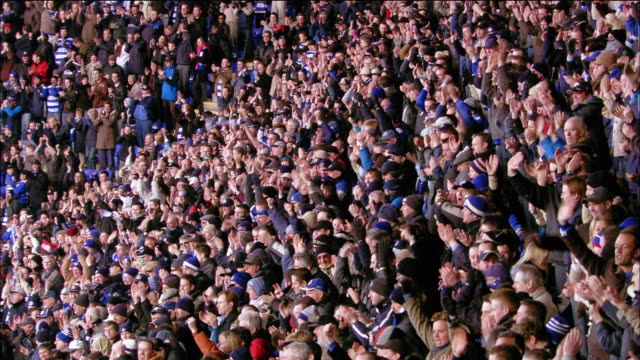 high angle wide shot zoom in pan crowd cheering during soccer match at madejski stadium / reading, england - crowd of people stock videos & royalty-free footage
