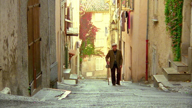 high angle wide shot zoom in pan senior man with cane walking up steep village road toward camera / biot, france - french culture stock videos and b-roll footage