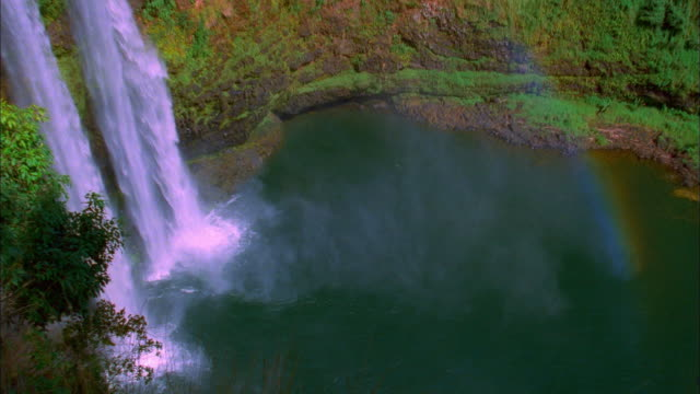 high angle wide shot zoom out waterfall and rainbow - isola di kauai video stock e b–roll