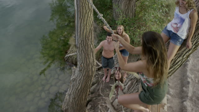 high angle wide slow motion shot of woman swinging into lake / mona, utah, united states - rope swing stock videos & royalty-free footage