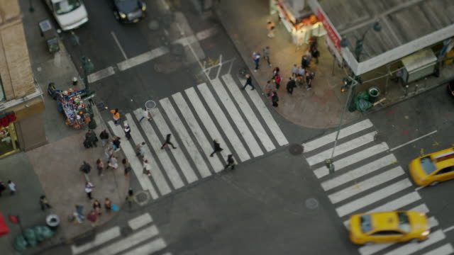 High angle wide time lapse shot of pedestrians in city intersection / New York, New York, United States