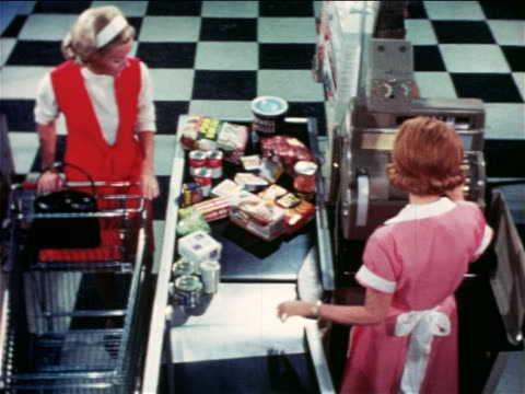 1965 high angle woman arranging groceries on conveyor belt as cashier rings them up / educational