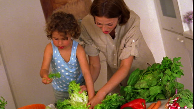 CANTED high angle MS woman + child putting lettuce in bowl for salad in kitchen