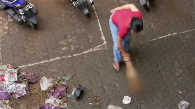 vídeos y material grabado en eventos de stock de high angle woman cleaning up at ubud street market with small broom / bali, indonesia - barrer
