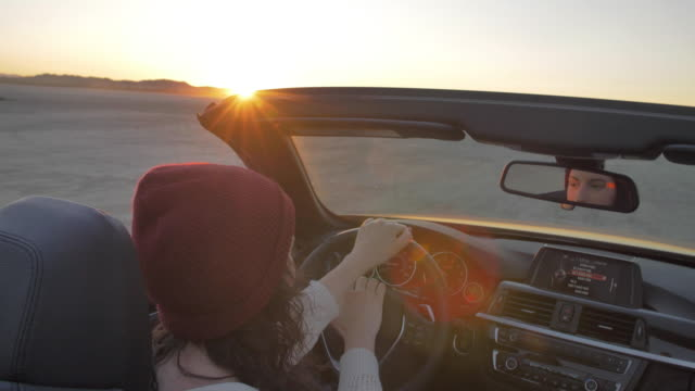 vidéos et rushes de high angle, woman drives car in california desert at sunset - aller tranquillement