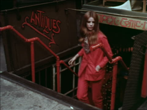 1969 high angle woman exiting antique store + walking up stairs to sidewalk / Greenwich Village, NYC