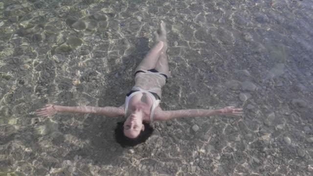 vídeos y material grabado en eventos de stock de high angle, woman in bikini floats on shallow water in croatia - cultura croata
