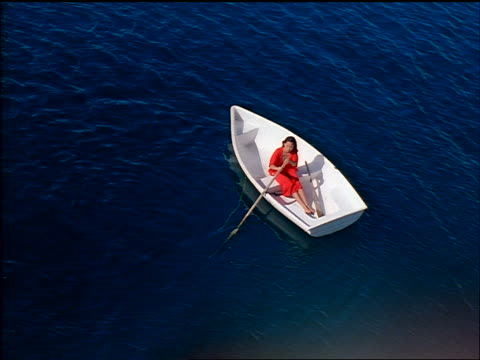 high angle woman in red dress rowing white rowboat in blue water - anno 1998 video stock e b–roll