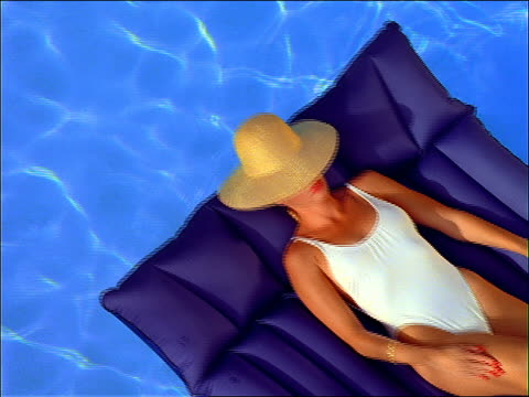 high angle woman in straw hat + white swimsuit lying on inflatable raft in swimming pool - sonnenbaden stock-videos und b-roll-filmmaterial