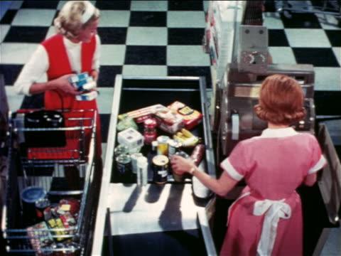 1965 high angle woman putting groceries on conveyor as cashier checks her out / educational