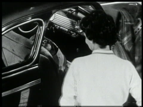 b/w 1959 high angle woman putting grocery bag in front seat of car / has difficulty shutting door - 1959 stock videos & royalty-free footage