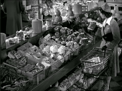 b/w 1944 high angle woman shopping in produce section of grocery store - supermarkt stock-videos und b-roll-filmmaterial