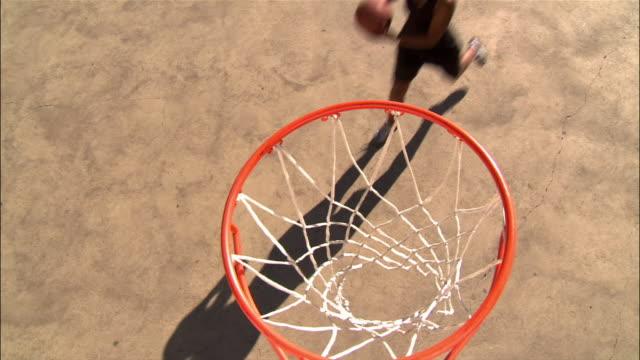 high angle woman throwing basketball that passes over net/ dallas, texas - バスケットボールのシュート点の映像素材/bロール