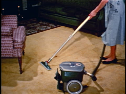 1950 high angle woman vacuuming carpet with vacuum cleaner - lavori di casa video stock e b–roll