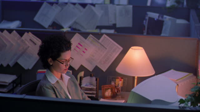 high angle woman working at computer + drinking coffee in cubicle with lamp on / other cubicles in dark in background - office partition stock videos & royalty-free footage