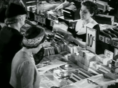 b/w 1938 high angle women buying paper products from saleswoman in 5 and 10 store / industrial - discount shop stock videos & royalty-free footage