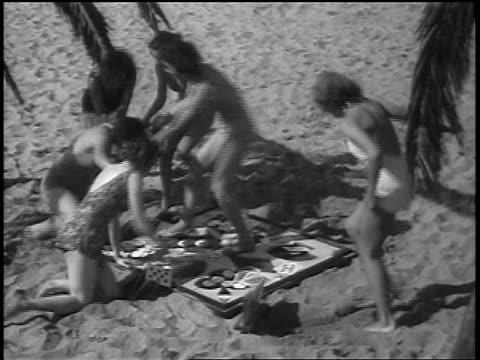 vídeos y material grabado en eventos de stock de b/w 1937 high angle women in swimsuits grabbing one woman in card game on beach / newsreel - traje de baño de una pieza