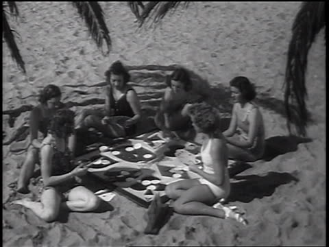 b/w 1937 high angle women in swimsuits playing cards on beach / newsreel - 1937 stock-videos und b-roll-filmmaterial