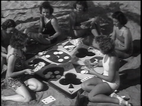 vídeos de stock e filmes b-roll de b/w 1937 high angle women in swimsuits playing cards on beach / newsreel - 1930