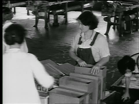 b/w 1929 high angle women putting packages of wax into box in factory / newsreel - 1929 stock videos and b-roll footage