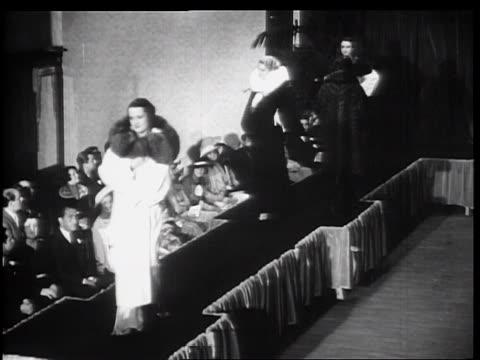 b/w 1934 high angle women walking up + down fashion runway modeling winter 1935 fur coats - 1934 stock-videos und b-roll-filmmaterial