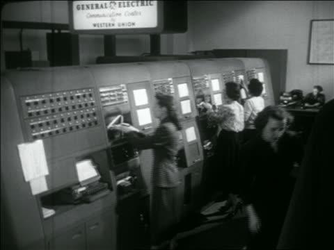 b/w 1956 high angle women working on large telegraph machines / western union - telegraph machine stock videos & royalty-free footage