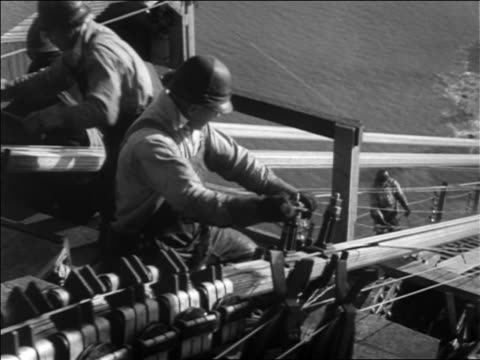 B/W 1936 high angle worker tightening wire atop Golden Gate Bridge construction / SF / newsreel