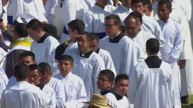 high angle, worshipers take communion outside in venustiano carranza stadium during pope francis visit in morelia, mexico - morelia video stock e b–roll