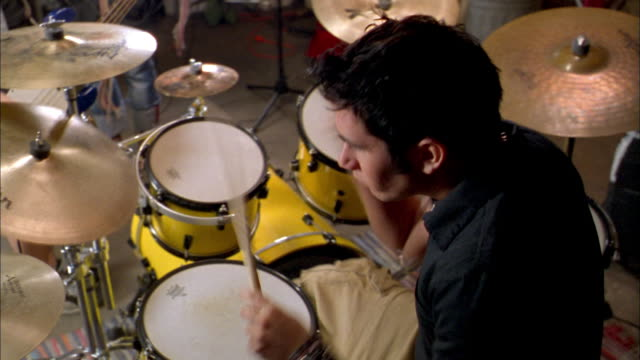 high angle young male drummer performing w/rock band - schlagzeuger stock-videos und b-roll-filmmaterial