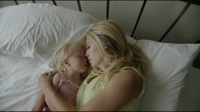 stockvideo's en b-roll-footage met high angle zoom in close up shot of mother and daughter sleeping on bed / cedar hills, utah, united states - moe