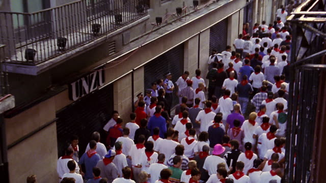high angle zoom in crowd of people running in street / running of the bulls / pamplona, spain - crowd running scared stock videos & royalty-free footage