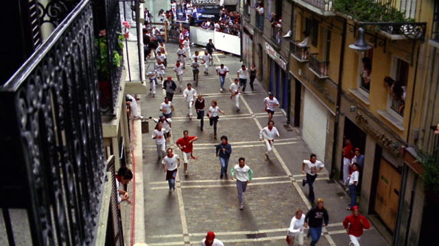 high angle zoom in crowd of people running on city street / Running of the Bulls / Pamplona, Spain