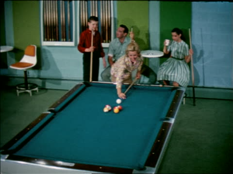 1963 high angle zoom in family watching as woman shoots pool / hits all balls into pockets in trick / zoom out