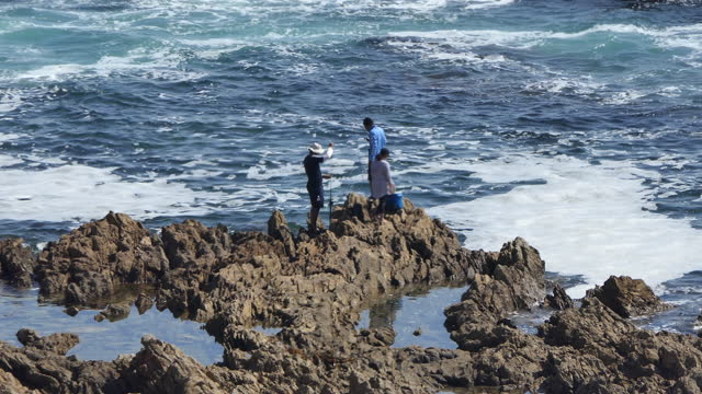 high angle zoom in on fishermen fishing off rocks the california coast, white point, rancho palos verdes, southern california, - palos verdes stock videos & royalty-free footage