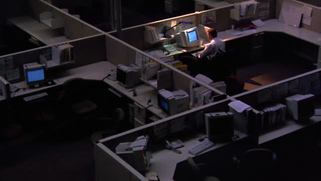 stockvideo's en b-roll-footage met high angle zoom in one man working late at computer with desk lamp in dark office with cubicles - overwerkt